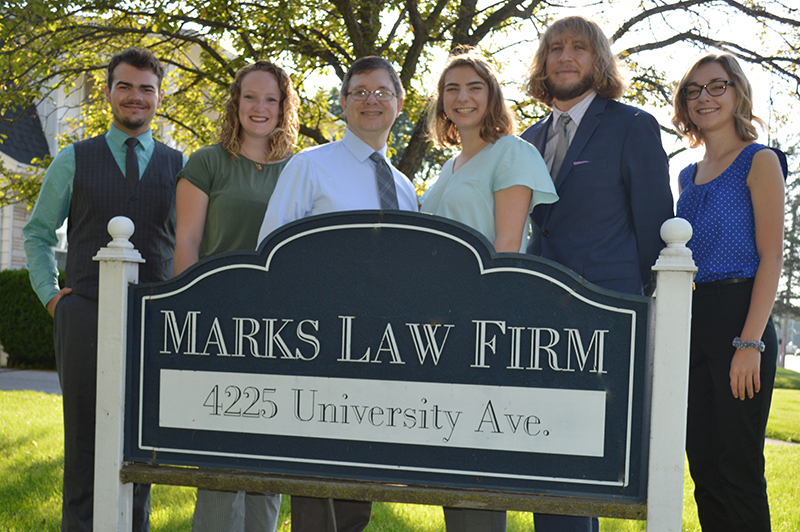 Marks Law Firm Lawyers standing in front of the Marks Law Firm business sign